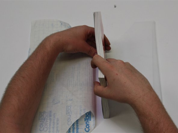 Using a rolling motion, slowly stick the rest of the spine to the laminate.