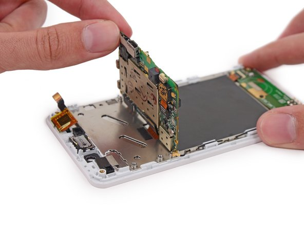 Image 2/2: The rear-facing camera may be adhered to the display assembly. Try to pry it and the motherboard up together.