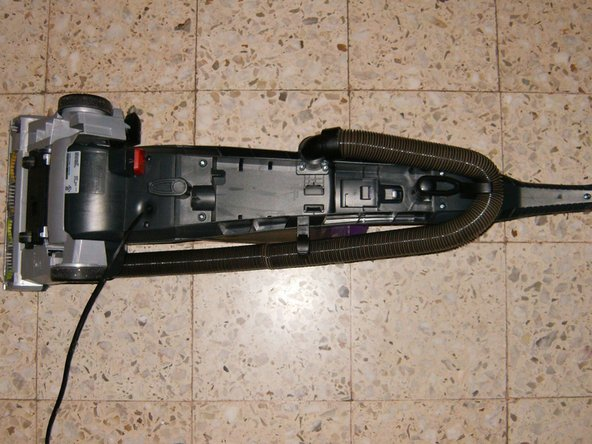 Unplug the vacuum and turn it over so the bottom of the vacuum can be accessed