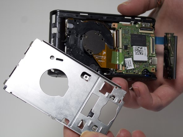 Remove 2 3mm screws from the metal plate covering the motherboard and lens using a Phillips #00 screw driver.
