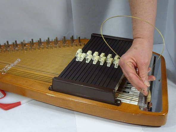 Make a loop with the string and slide it between the strings and chord bar. Draw the string across the bridge pin and past the tuning peg but do not thread through the hole yet.
