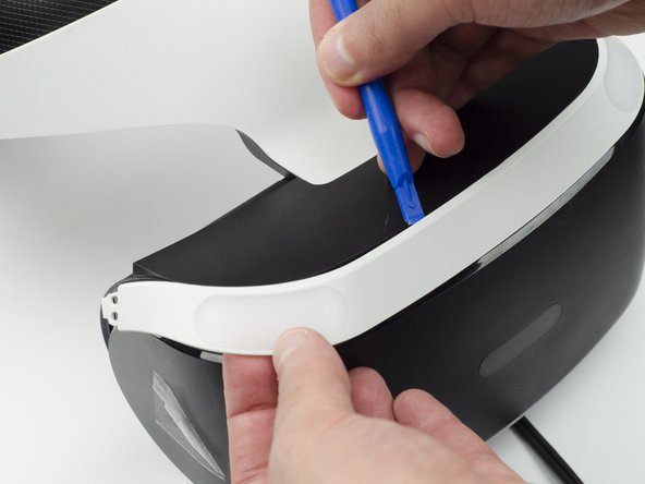 Use the plastic opening tool to pry the top white plastic panel free from the headset.