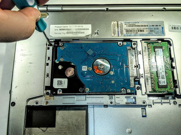 Remove the three 5mm Phillips head screws that secure the Hard Drive bay to the back panel.