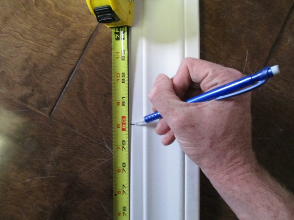 Image 1/1: Using the measurement from the previous step, mark the appropriate length on the trim to be installed.