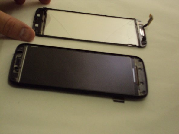 Image 3/3: Continue prying the screen from the casing until it can be fully removed.