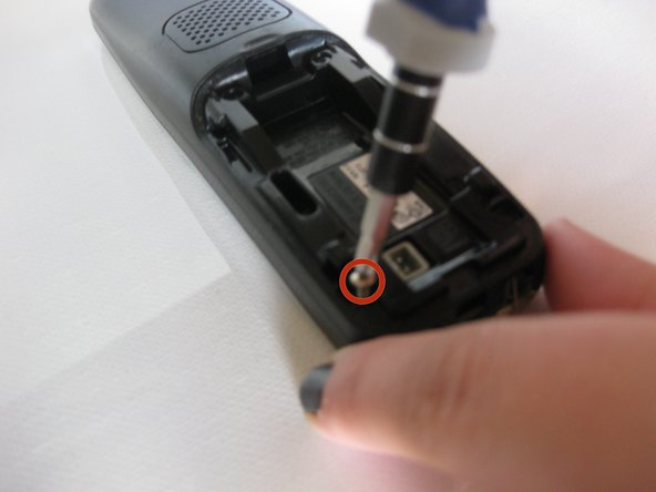 Using a phillips #1 screw driver, remove the two .9 mm phillips screws on the back of the device located on both sides of the battery pack.
