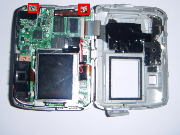 Use a Phillips screwdriver to remove the two silver screws that connect the circuit board to the outer front casing.