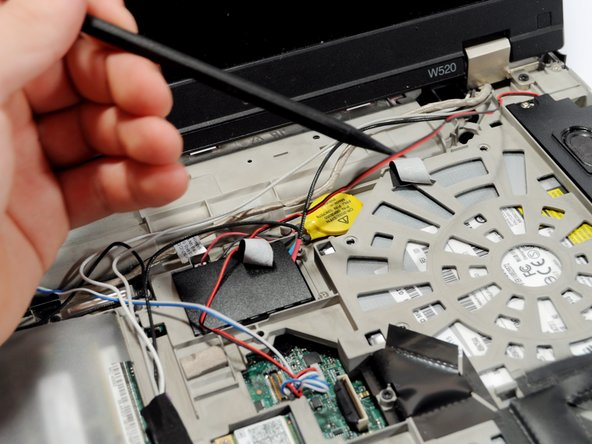 Using a spudger and your hand as needed, gently free the black and red wire from all constraints.