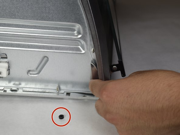 On the left side, push out the spring attachment while pulling on the door in an upward, outward, location