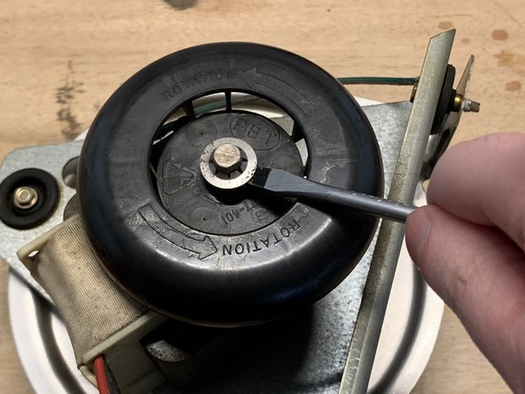 Take your flathead screwdriver and carefully pry off the circular clip from the cooling fan.