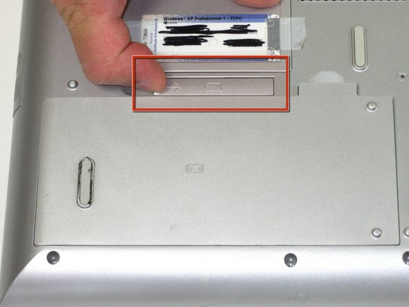 Flip the laptop over. Slide the battery release tab to the right.