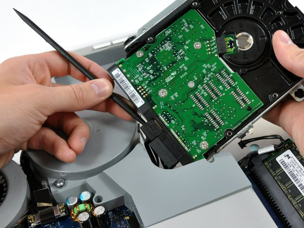 Insert the flat end of a spudger into the gap between the SATA data connector and the hard drive.