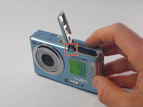 Push the small, plastic arm out of the way to free the battery.