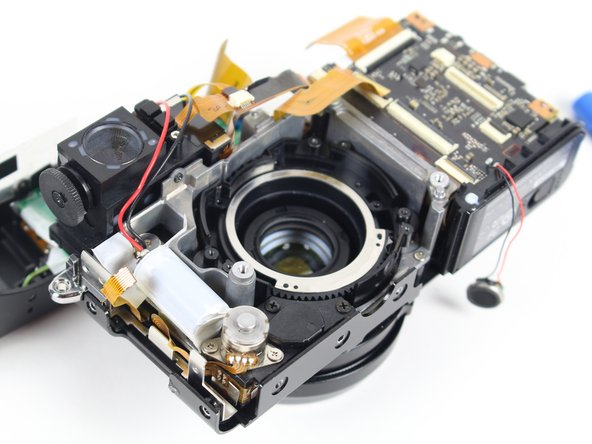 Once the lens has been taken off, flip the camera over and unscrew the two 4.0 mm screws on the front of the camera, next to the lens cover.