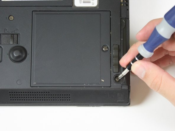 Flip to the back of the Thinkpad and focus on the screw in the bottom left corner of the Thinkpad.
