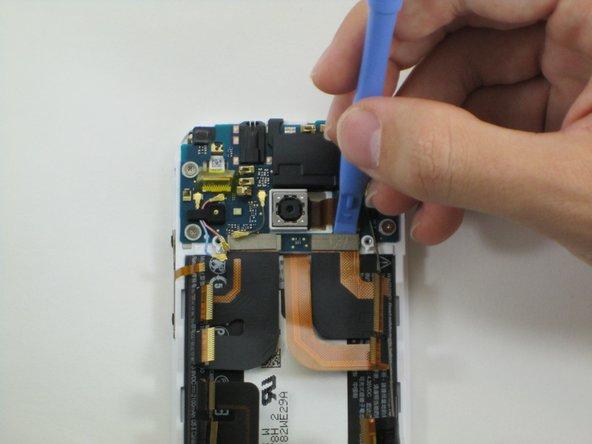 Verwende ein schmales Hebelwerkzeug aus Plastik, um die Stecker der beiden Flachbandkabel an der Unterseite der oberen Platine zu entfernen.