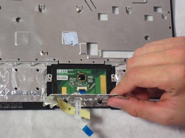 Lift the metal plate up to expose the trackpad.