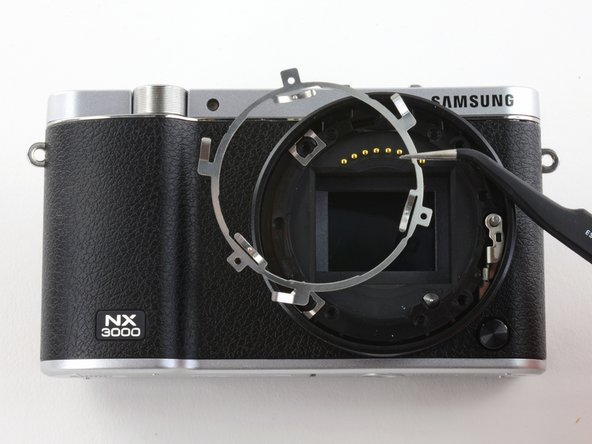 Use tweezers to remove the black plastic ring  and small metal ring inside the lens assembly.