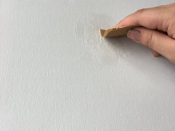 Make sure you have some solid surface behind the area being sanded to avoid creating bumps and deformities in the canvas.