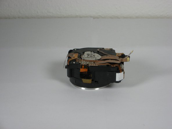 Image 1/2: The ribbons on the left and bottom of the assembly simply rest on the camera housing.