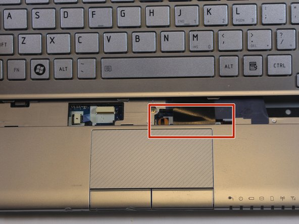 Image 1/2: Using a spudger, press on the clips to release the cable.