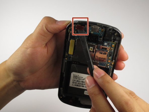 Using the prying tool, carefully lift and snap off the flex cable from the top of the phone.