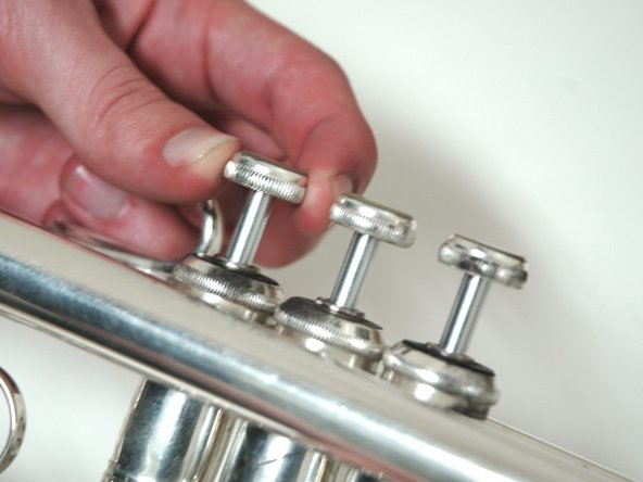Insert the valve into the trumpet, and screw in the top clockwise.