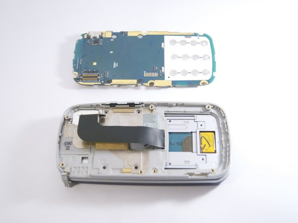 Grip the motherboard and gently pull to separate it from the rest of the phone.