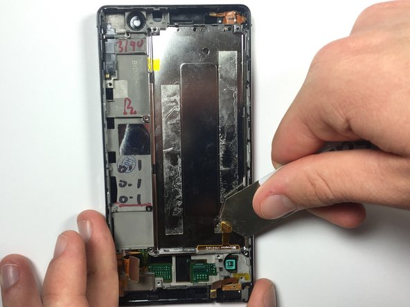 Image 1/2: This piece will not come off completely, but it must be separated in order to remove the display.