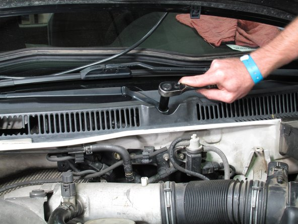 Use a socket wrench to release the passenger-side windshield wiper locking nut.
