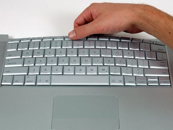 Image 1/1: Maintaining your hold on the keyboard, lay the casing flat and gently bow the keyboard until the two tabs on either side of the keyboard come free.