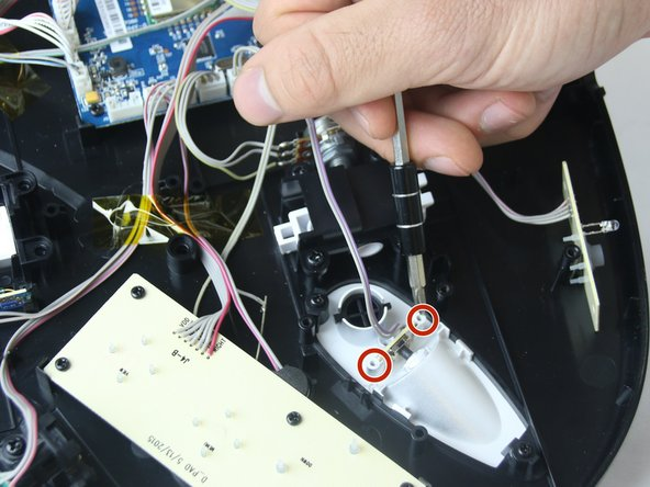 Image 1/1: Remove the two 5mm black screws (circled in red) holding the circuit board in place using a size J1 philips head screwdriver. The component should now slide out vertically.