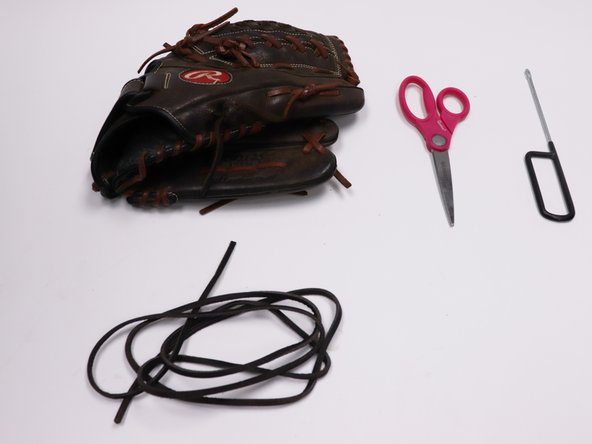 Gather your materials; the glove, scissors, new thread, and the Glove Lacing Tool