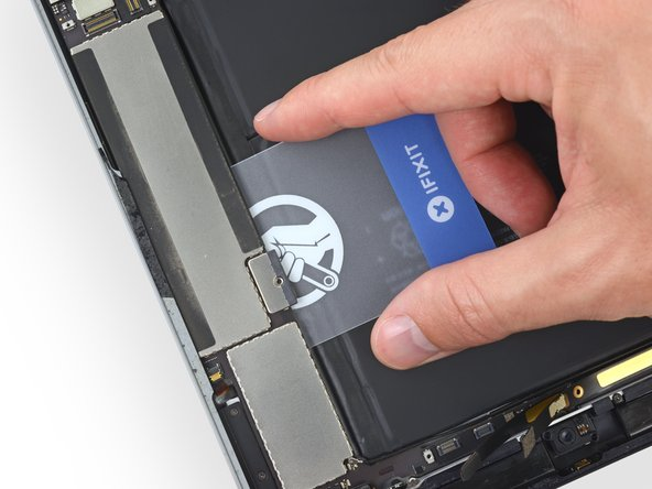 As you push through the adhesive at the outer edge of the logic board, be careful not to damage the upper button assembly ribbon cable that you disconnected in Step 60. Position the card exactly as shown.
