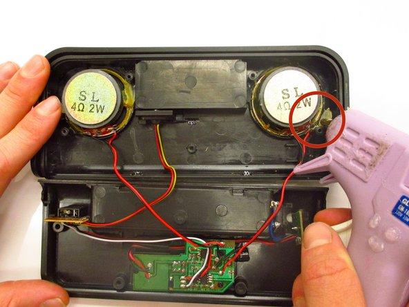 Using a hot glue gun, glue the new speakers in place