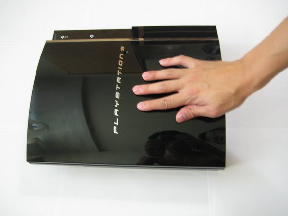 Image 1/3: Place your palm on the PlayStation 3 logo and slide the plastic front cover towards you and off of the outer plastic shell. Set it aside.