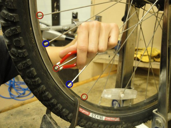 Image 1/2: Loosen the spokes that attach to the same side of the wheel as the caliper contact point. At the same time, tighten the spokes that attach to the opposite side of the wheel as the caliper contact point. To start, try a half turn for each of the spokes near the caliper contact point.