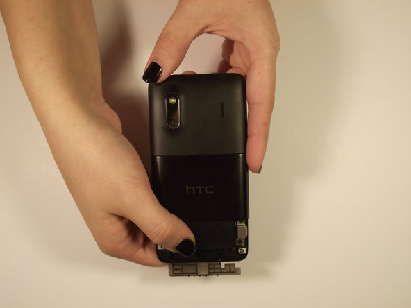 Image 1/2: Grab the bottom edge of the battery and pull it toward you