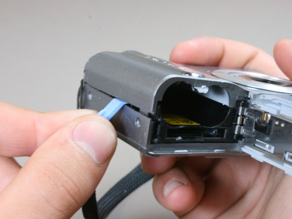 Slide the battery door open and 'slightly' open the side of the case with the iFixit plastic opening tool.