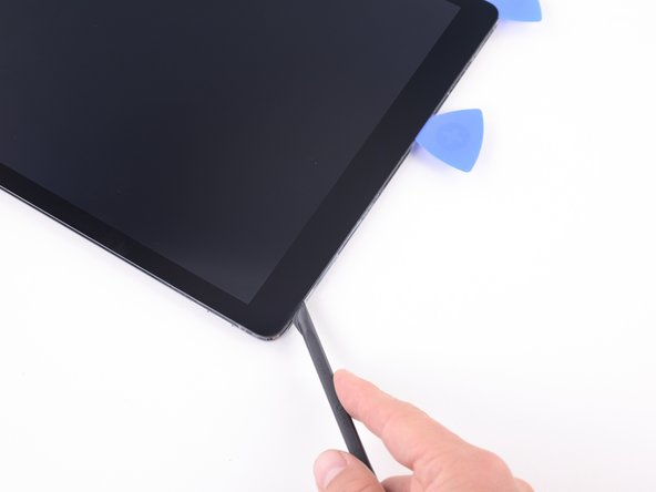 Image 3/3: Continue to slide the blade of the halberd spudger to the upper right corner of the iPad.