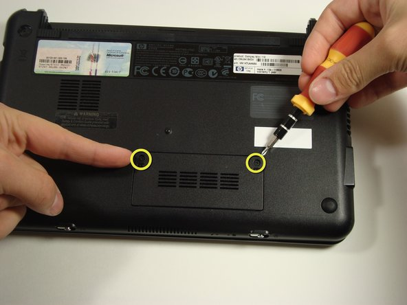 Find and remove the two screws on the bottom of your Compaq Mini covering the memory compartment.