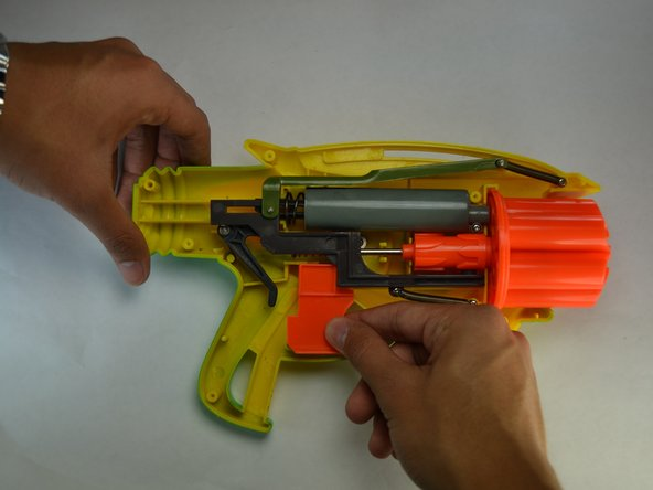 Grab the orange trigger and without misplacing the other parts of the blaster, remove the trigger.