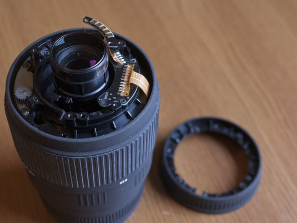 Unscrew the screws that hold the top plastic ring (which is part of the lens body) and remove it.
