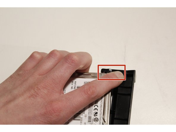 Image 3/3: Push on the plastic, and the hard drive will pop out.