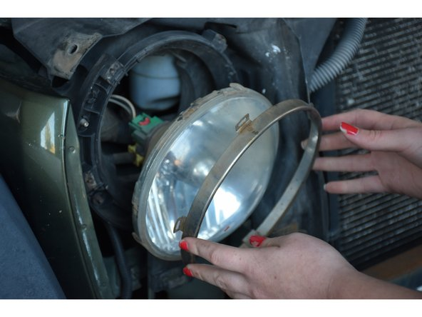 Use your hands to carefully remove silver ring from the headlight.