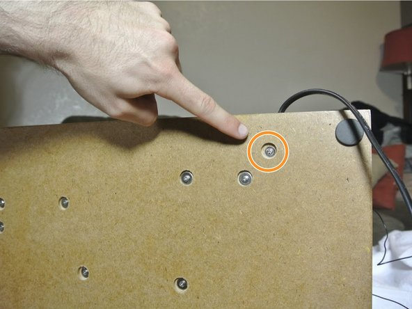 Pick up the device and locate the screw holding the small black peg to the device. Unscrew it and set the screw aside.