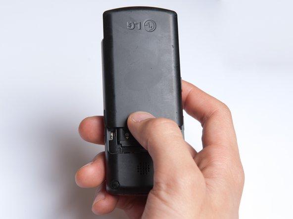 Au dos du téléphone, placez votre pouce sur les trois bosses soulevées et faites glisser le couvercle arrière vers le haut.