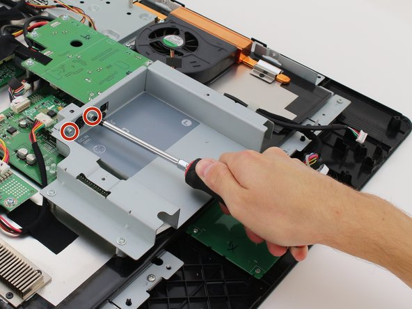 Remove the two 7.8mm Phillips #2 screws from the right back panel connected to the power port by turning the screwdriver counterclockwise.