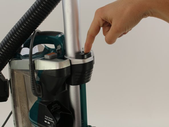 Press down on the wand release button and remove the  wand from the vacuum.