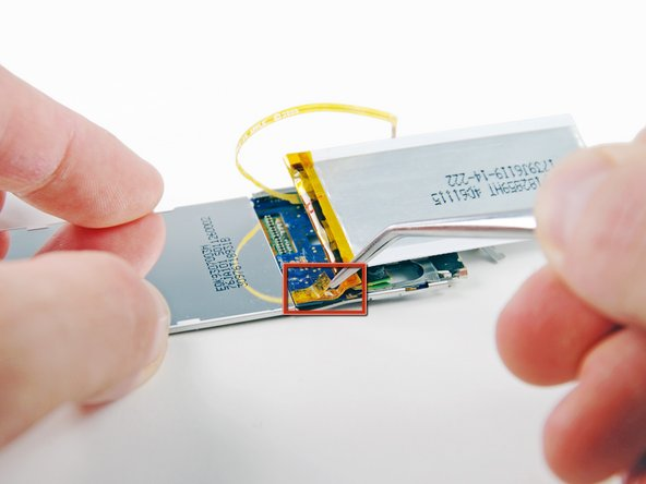Use a pair of tweezers to remove the orange tape that covers the three solder connections for the battery.